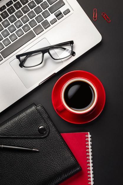空白の画面のラップトップコンピューター、ノートブック、マウス、一杯のコーヒー、その他のオフィスの黒いオフィスデスクテーブル。 Premium写真