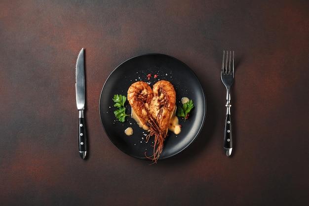 ハート型のエビと茶色の背景にワインのロマンチックなディナー。コピースペース平面図 Premium写真