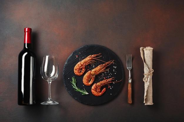 Романтический ужин с креветками в форме сердца и вином на коричневом фоне. вид сверху с копией пространства Premium Фотографии