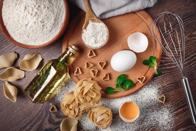 Пекарские ингредиенты. мука с сырым яйцом, масло для теста, макароны на деревянной доске Premium Фотографии
