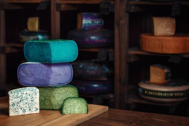 テーブルの上の金型とおいしいチーズブルーグリーンバイオレットチーズの様々な種類の木の板 Premium写真