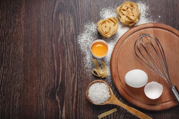 Пекарские ингредиенты. мука с сырыми яйцами для теста макароны на деревянном фоне Premium Фотографии