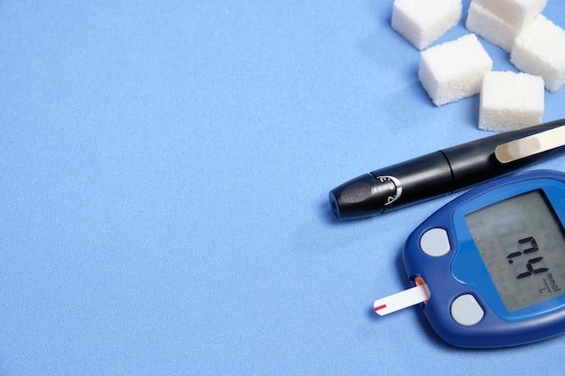 Глюкометр с тест-полоской на синем пространстве. место для текста, выборочный фокус Premium Фотографии