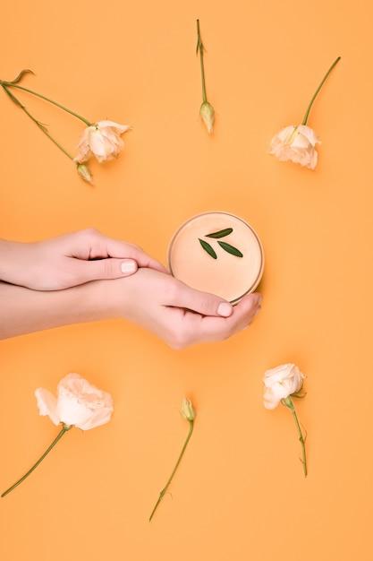 自然派化粧品によるスキンケア。女性の手は自然化粧品の瓶を保持しています。クリーム。エコ化粧品。手にクリーム。スキンケア。碑文のための場所。平置き Premium写真