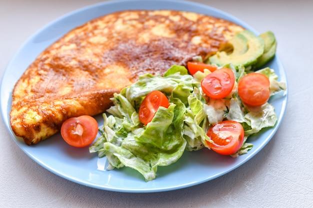 スクランブルエッグと新鮮な野菜。丸皿の上。キノコのオムレツ Premium写真