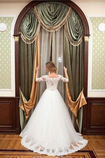 Девушка в белом свадебном платье у окна. на фоне окна стоит красивая женщина в белом свадебном платье с красивым макияжем и прической. Premium Фотографии