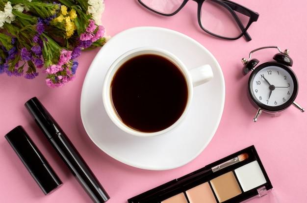 Кофейная чашка, будильник, цветы, тушь и очки на розовой поверхности. Premium Фотографии