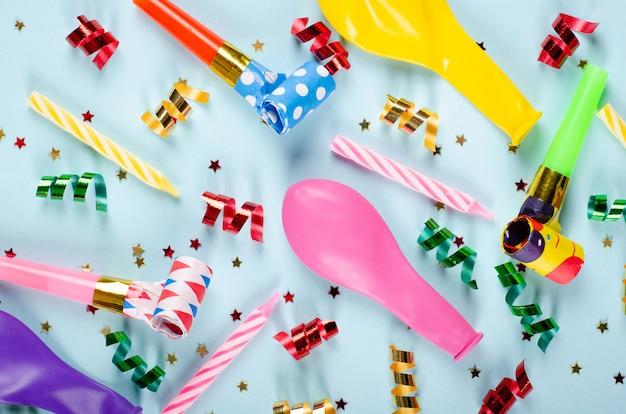 青色の背景、パーティー、お祝いの装飾の色の紙吹雪と気球の組成。 Premium写真