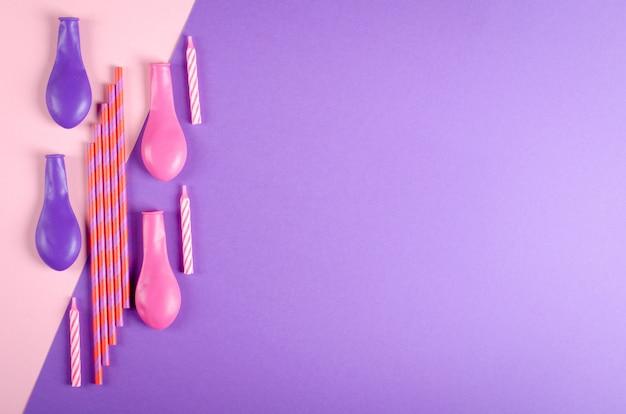 紫色の背景、パーティー、お祝いの装飾の色のキャンドルと気球の組成。 Premium写真