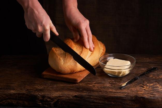 女性は黒のバターとボウルの近くの木製のテーブルで焼きたてのパンをカットします。 Premium写真