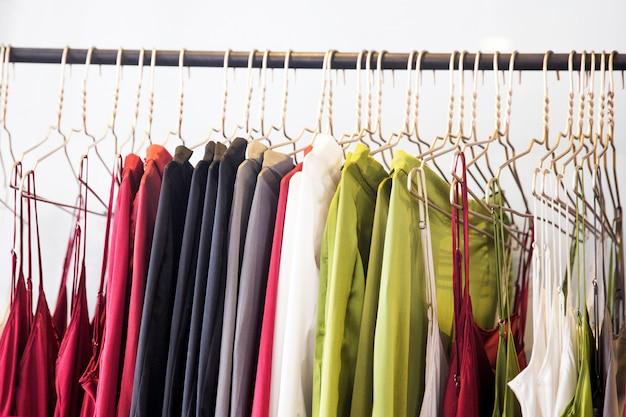 おしゃれな服が店にぶら下がっています Premium写真