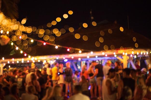 オーシャンビューのスイミングプールに閉じた友人と夕暮れ時のビーチパーティー。 Premium写真