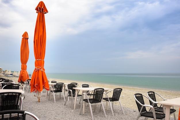 空のテーブルと椅子のあるビーチカフェ Premium写真
