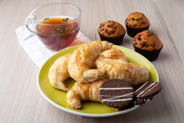 マフィン、紅茶、クロワッサン、キャラメルクッキー Premium写真