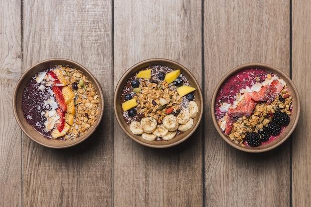Три веганские и полезные десерты на деревянном столе Premium Фотографии