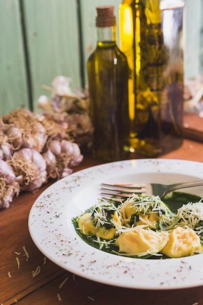 パルメザンチーズ、ニンニク、オリーブオイルと木製のテーブルの上のソレント Premium写真
