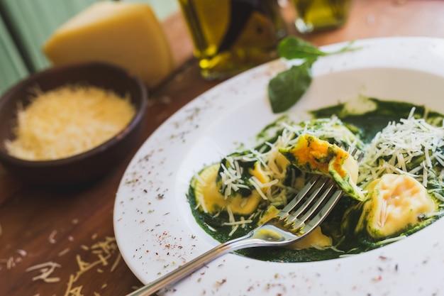 パルメザンチーズと木製のテーブルの上のオリーブオイルとソレント Premium写真