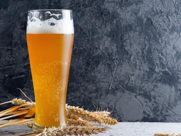 暗いコンクリート背景と小麦の耳に小麦ビールのグラス Premium写真