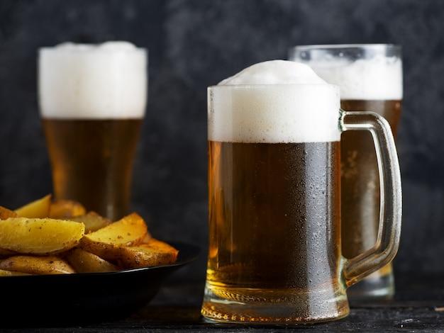 Три бокала светлого пива и деревенский картофель на темном столе Premium Фотографии