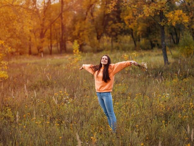 秋の森を歩くオレンジ色のパーカーで幸せな若い女性。ライフスタイル Premium写真