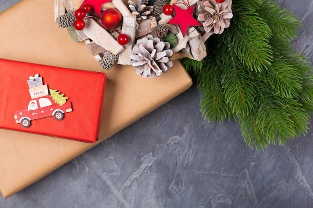 クリスマスの組成物。ギフトボックス、モミの木、サンタと木製のおもちゃの車、テキストクリスマス。概念。平干し、コピースペース Premium写真