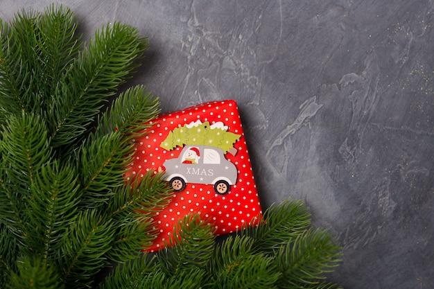クリスマスの背景。ギフトボックス、モミの木、サンタと木製のおもちゃの車、テキストクリスマス。概念。平干し、コピースペース Premium写真