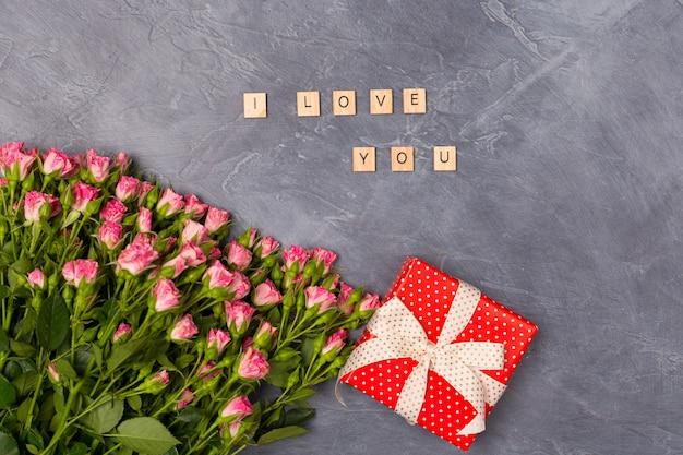 ピンクのスプレーバラ、赤いボックスのギフト、灰色の背景にあなたを愛しています。女性の日母の聖バレンタインのコンセプト Premium写真