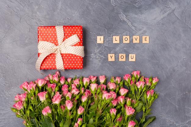 ピンクのスプレーのバラ、ギフトの赤い箱、灰色の背景上のテキストが大好きです。女性の日母の聖バレンタインのコンセプト Premium写真