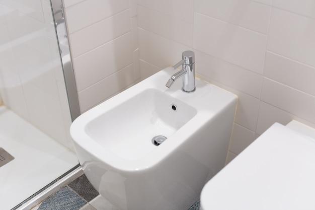 Белое биде прикручивается к бежевой изразцовой стене в ванной, крупный план. белое биде с хромированной мешалкой на кафельном полу Premium Фотографии