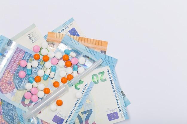Сортированные пилюльки, таблетки и шприц фармацевтической медицины на евро ес на белой предпосылке. концепция здравоохранения. кризис. деньги. свободное место. копировать пространство Premium Фотографии