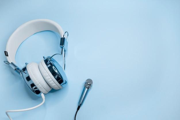 青いヘッドフォンとマイクの音楽の背景。 Premium写真