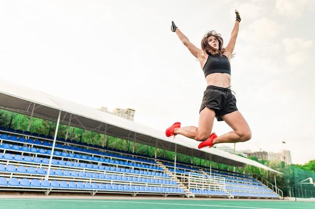 Красивая здоровая спортивная женщина прыгает на стадионе высоко в воздухе Premium Фотографии