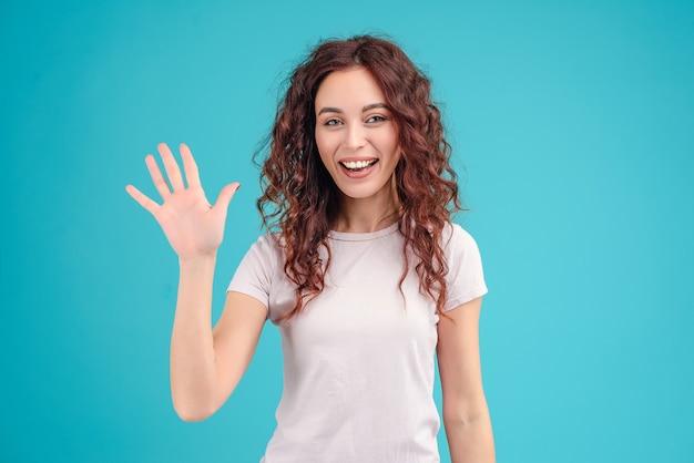 魅力的な女性のこんにちはを振るとターコイズブルーの背景に分離された手の手のひらを示す Premium写真