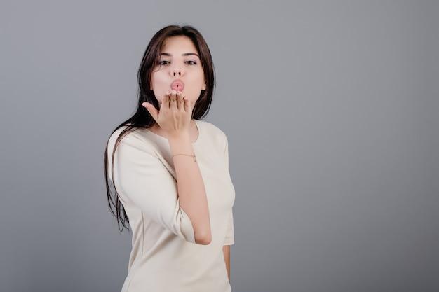 灰色で分離された手でスムーチキスを送信する美しいブルネットの女性 Premium写真