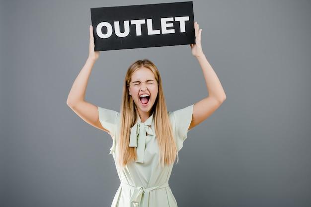 Счастливая кричащая девушка при знак выхода изолированный над серым цветом Premium Фотографии