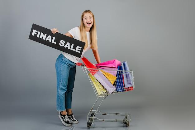 最終販売サインと灰色で分離されたカラフルなショッピングバッグと手押し車と笑顔の幸せな女 Premium写真