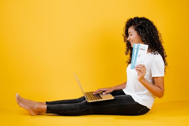 黄色で分離されたラップトップと飛行機のチケットで座っているかなり若い黒人アフリカ女性 Premium写真