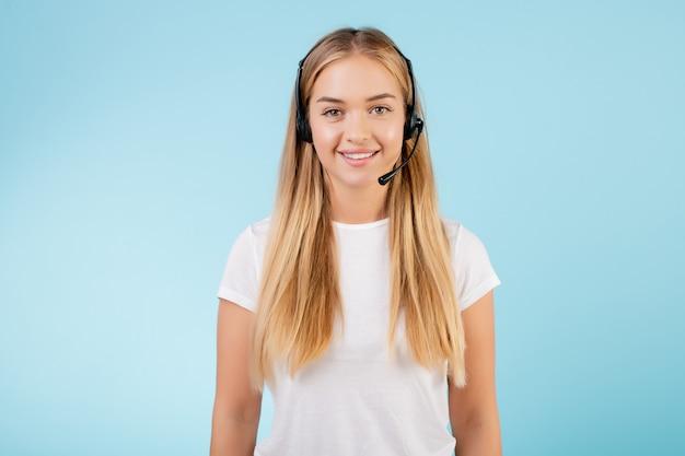青で分離されたヘッドセットとフレンドリーな笑顔金髪コールセンターオペレーター Premium写真
