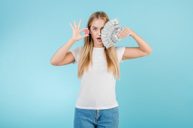 オンラインカジノと青で分離されたお金からポーカーチップを持つ魅力的な若いブロンドの女の子 Premium写真
