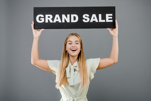 灰色で分離されたグランドセール記号で笑顔の幸せな女 Premium写真