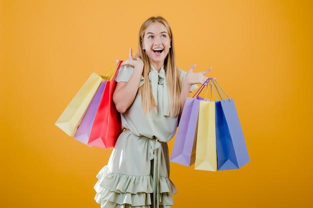 黄色で分離されたカラフルなショッピングバッグに笑みを浮かべて美しい若いブロンドの女性 Premium写真