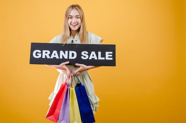 グランドセールサインと黄色で分離されたカラフルなショッピングバッグと幸せな笑顔金髪少女 Premium写真