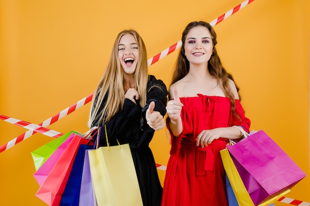 カラフルな買い物袋と黄色で分離された信号テープと美しい若い女性 Premium写真
