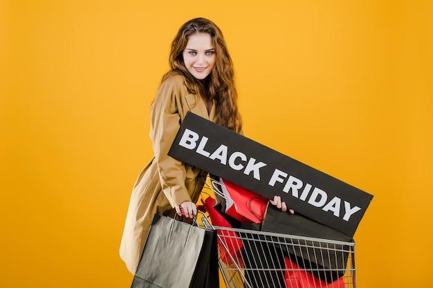 黒い金曜日記号と黄色で分離された手押し車でカラフルなショッピングバッグと秋のトレンチコートの若い女性 Premium写真