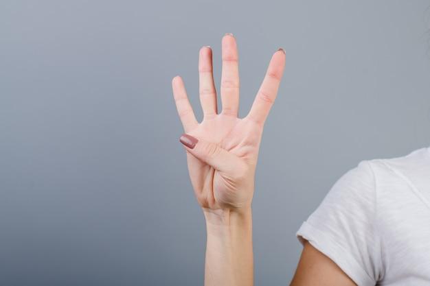 Женская рука в кулак, показаны четыре пальца, изолированных на серый Premium Фотографии