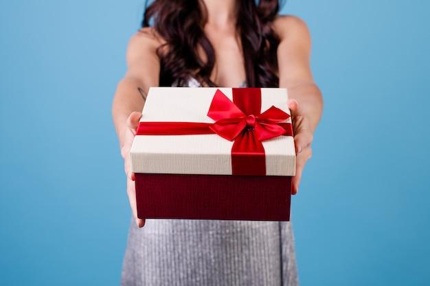 青で分離されたドレスを着て赤いリボンとギフトボックスで興奮した女性 Premium写真