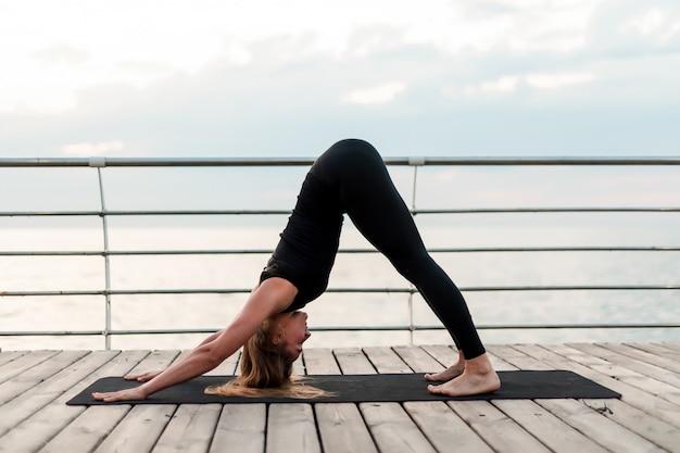 朝の日の出、海のそばのヨガのアーサナをやって、スポーツやフィットネスの練習を柔軟な女性 Premium写真