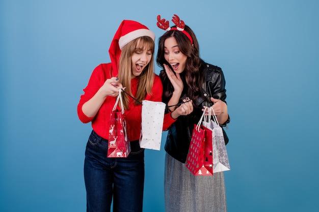 クリスマス帽子と青で分離された冬の服を着てカラフルなショッピングバッグにプレゼントを持つ女性 Premium写真