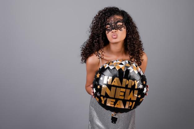 灰色で分離された仮面舞踏会マスクを着て新年あけましておめでとうございますバルーンと美しい黒の女の子 Premium写真