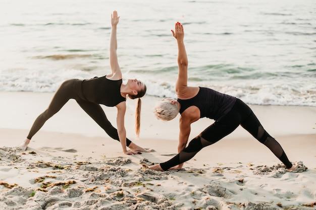 Женщины занимаются фитнесом синхронно позируют в йоге асаны на пляже у моря Premium Фотографии